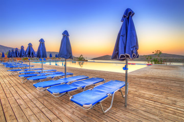 Sunrise at Mirabello Bay with empty deck chairs, Greece