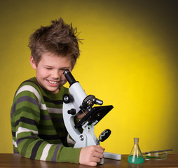 Smiling boy with a microscope on yellow   background