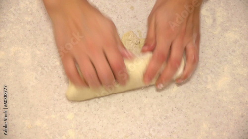 Woman kneading dough with hands for pizza