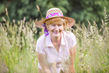Senior Peasant Woman in Meadow smiling. Mature Friendly Lady