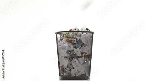Throwing paper into the waste basket: Bin filled by documents