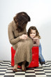 Cute little girl posing in studio with her mother