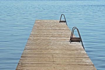 Long wooden dock reaching out into blue inviting waters