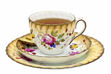 Tea in an antique china cup with saucer and dessert plate.