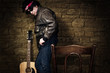 Musician stands against wall in shallow depth of field with an e