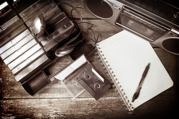 Old cassette tapes, cassette player and blank notebook on wooden