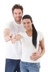 Happy young couple smiling showing thumb up