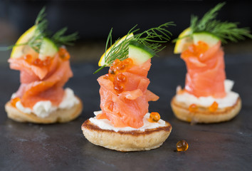 Blini with smoked salmon and sour cream, garnished with dill. Cl