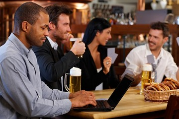 Young man using laptop at pub