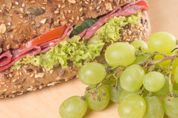 belegtes Brötchen und Weintrauben