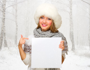 Young girl with empty poster at snowy forest