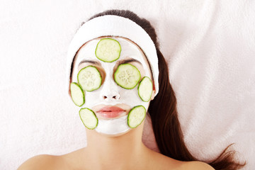Young woman with cucumber slices on the face