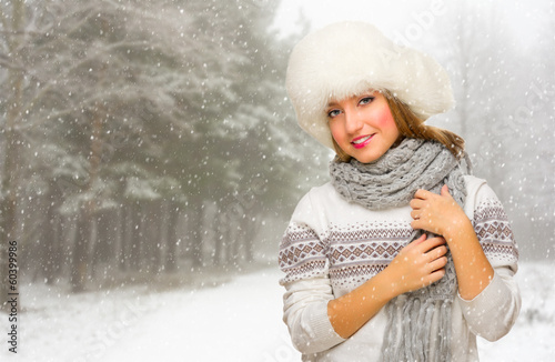 Young girl with hat at snowy forest