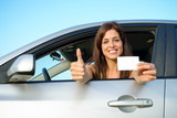 Successful girl in car with driving license