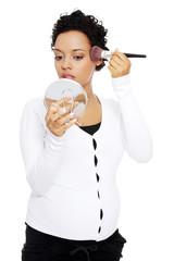 Pregnant woman doing a makeup.
