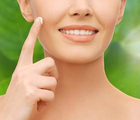 closeup of woman hand applying moisturizing cream
