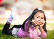 Little asian girl resting on green grass