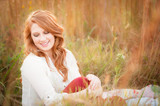 beautiful young red haired female in a field smiling