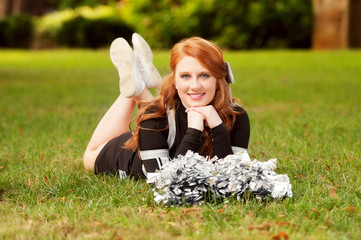 beautiful young red headed female cheerleader lying in the grass