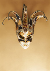 Venetian carnival mask on golden surface