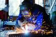 Leinwandbild Motiv Schweißer einer Werkstatt schweißt Metall