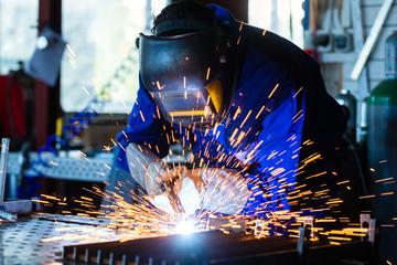 Schweißer einer Werkstatt schweißt Metall