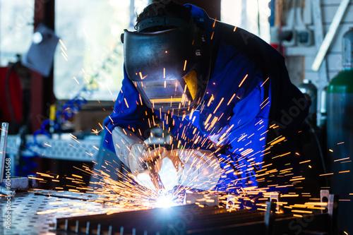 Leinwanddruck Bild Schweißer einer Werkstatt schweißt Metall