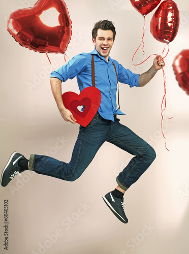 Laughing and jumping man with valentine's balloons