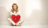 Alluring blonde girl holding red heart
