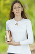teenage girl dressed in white with books