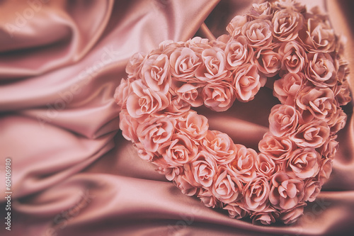 Heart made of pink roses on satin