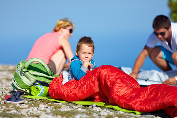 kid with parents camping in mountains
