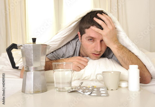 Leinwanddruck Bild Man with headache and hangover in bed with tablets