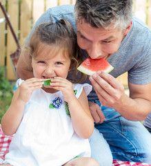 Father and little girl having watermelon on a picnic