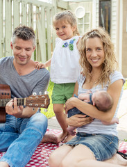 Father playing guitar on a family picnic