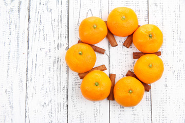 Ripe sweet tangerines and spices, on wooden background