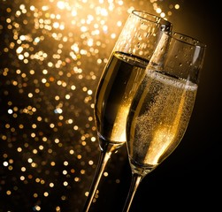 champagne flutes on dark golden bokeh background