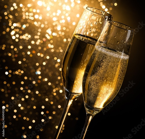 Foto op Plexiglas Alcohol champagne flutes on dark golden bokeh background