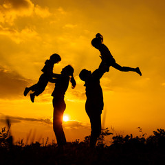 Happy  family playing on the  road in the  sunset time. Evening