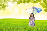Beautiful woman holds umbrella in green field