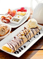 crepe with bananas and ice cream on white plate