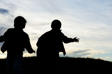 Happy children silhouettes playing in park