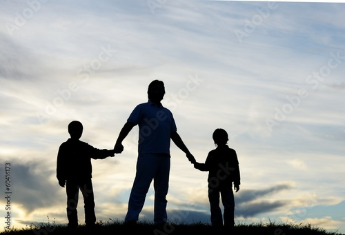 Father with sons playing on sunset meadow