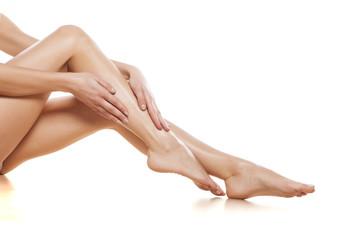 woman apply cream on her bare feet