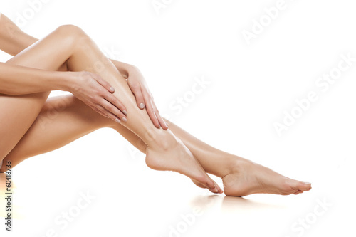 woman apply cream on her bare feet