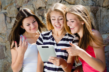 Three happy teen girl friends looking on tablet pc
