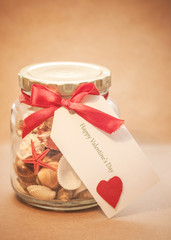 Background Glass jar with shells, red ribbon and card blank