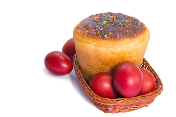Red Easter eggs and Easter bread in a basket on a white backgrou