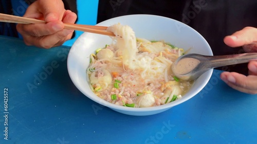 A man is eating Thai noodle with seasoning pork.