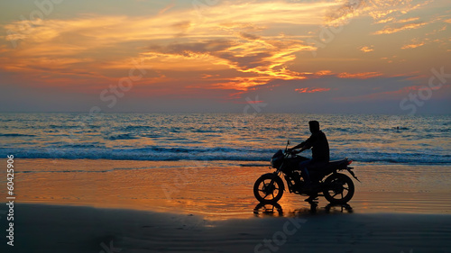 Foto op Plexiglas Motorsport Motorcyclist at sunset on the beach. Abstract background
